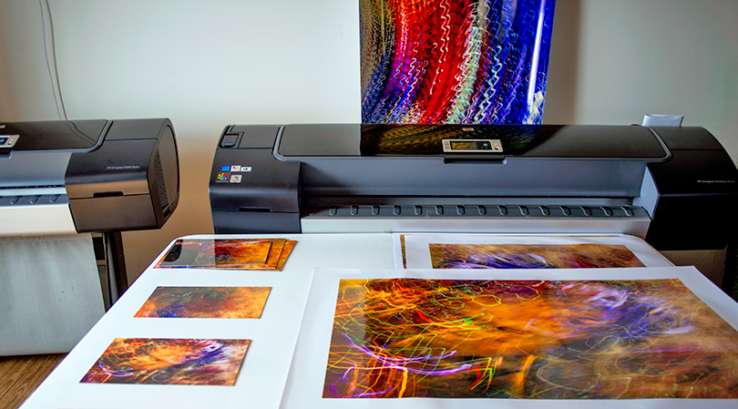 In Lindquist Studios' print studio, dye-sub proof prints (left) and proof prints from Mark's HP Z3200ps printer (right). Full-size print (background) is to check for color, noise, and sharpness of another image.