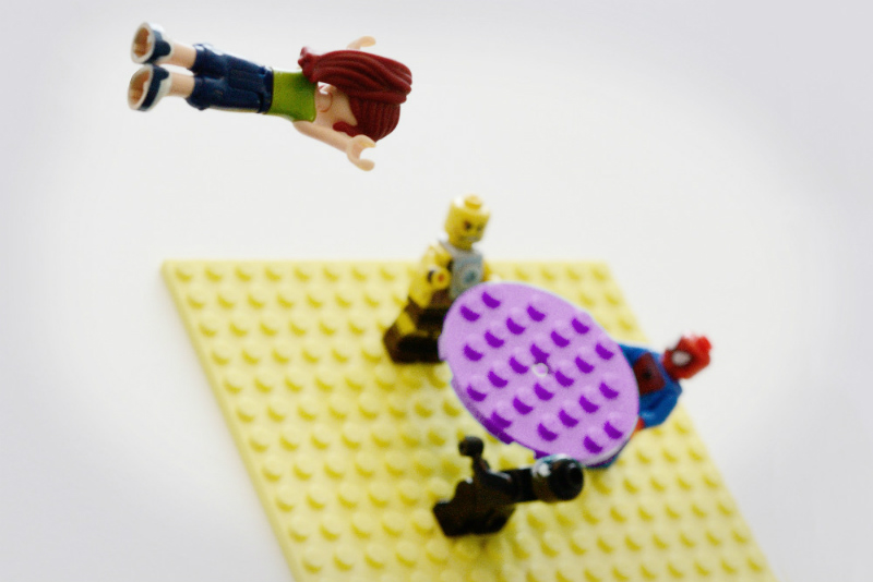 lego girl leaping from a height into net held by other lego people