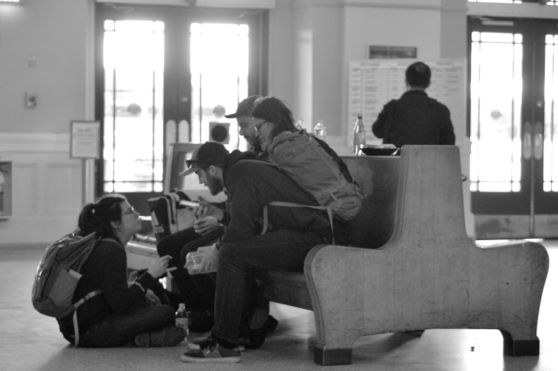 A group of young adults waits in a bus terminal, chatting.
