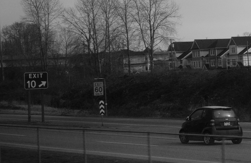 A tiny car approaches a highway exit ramp