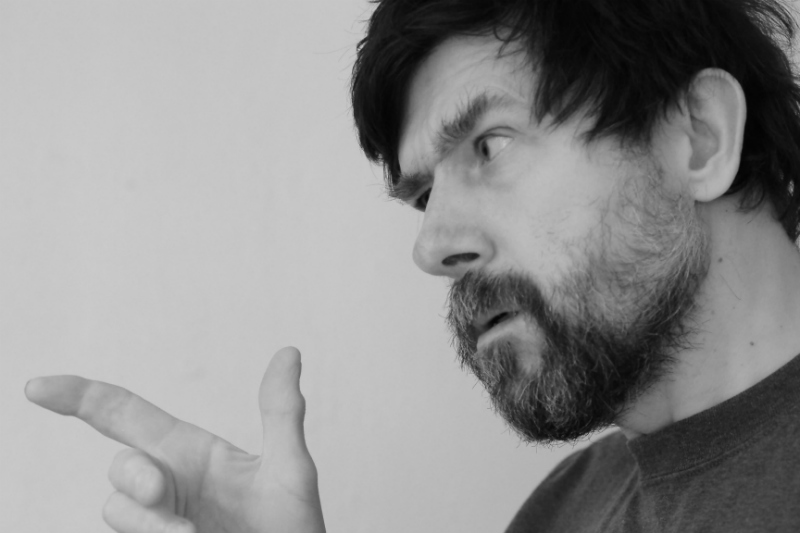 A man appears to be arguing with someone, glaring and pointing a finger