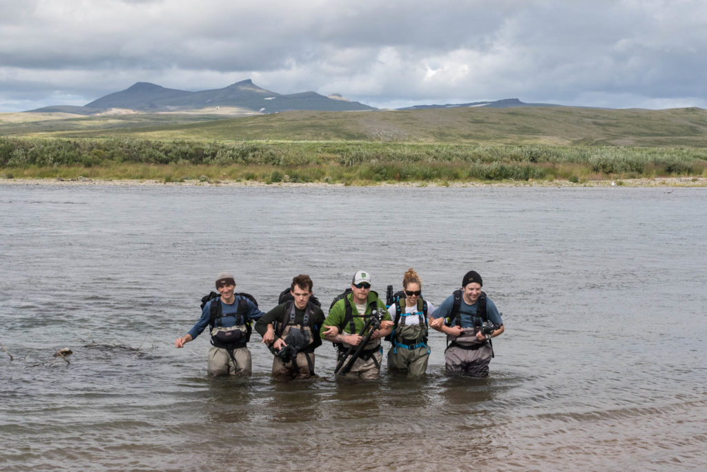 The receipients of the 2016 Art Wolfe Next-Generation Photographers Grant cross a river with professional photographer and workshop leader Gavriel Jecan (left).