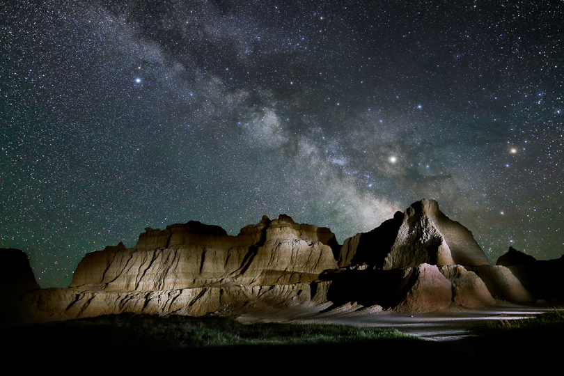 The Milky Way over the Badlands. Nearly all of my night sky photos are done in two pieces. The sky was exposed using a tracking mount to render the stars as sharp dots rather than streaks. The foreground was exposed with the tracking mount turned off and I light painted the hills using an LED flashlight. The two pieces are then combined in Photoshop.