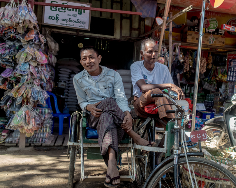 Shot with DXO ONE Camera. Men at the Trishaw, at Pyinmana Market, NayPyiTaw. The Trishaw is a three-wheeled rickshaw that is hugely popular for local transport across Myanmar.