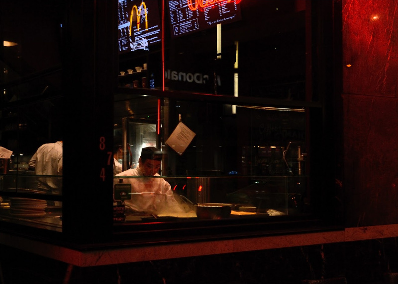 An asian man makes a crepe in a shop window.