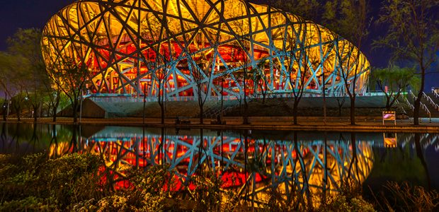 """The National Stadium in Beijing, also known as """"The Birds Nest"""", reflected on water."""