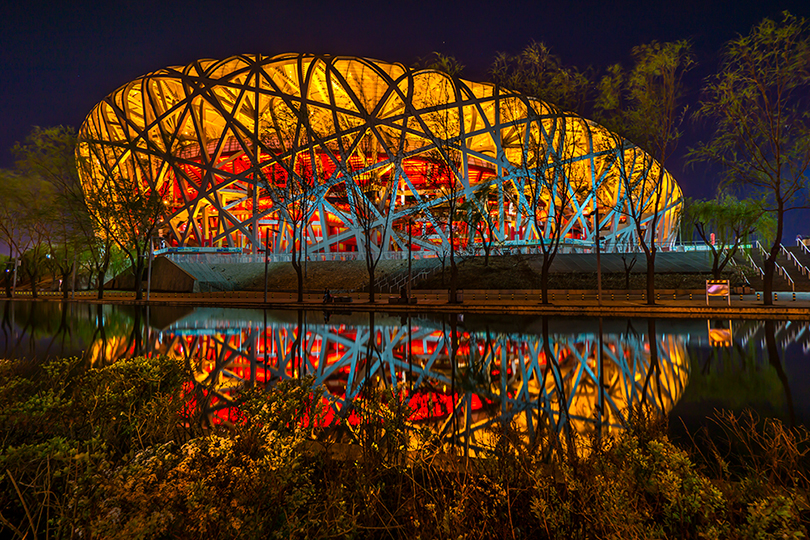 "The National Stadium in Beijing, also known as ""The Birds Nest"", reflected on water."