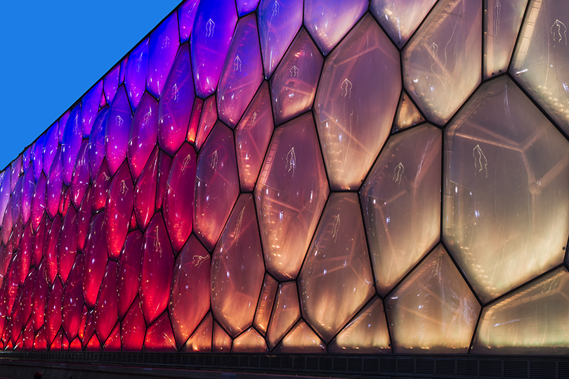 "The National Aquatics Center in Beijing, also known as ""The Water Cube"", viewed while the soap bubble like façade changes colors."