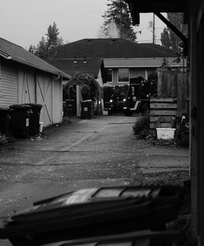 A garbage truck appears around the corner at the top of the alley.